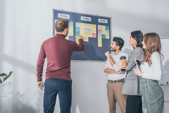 back view of scrum master pointing with finger at board with letters near multicultural coworkers