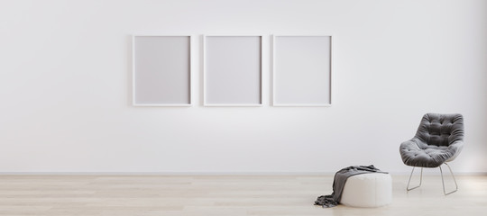 three blank poster frames in room with white wall and wooden floor with white pouf and grey modern armchair. Bright room interior with empty frames mockup. 3d rendering.