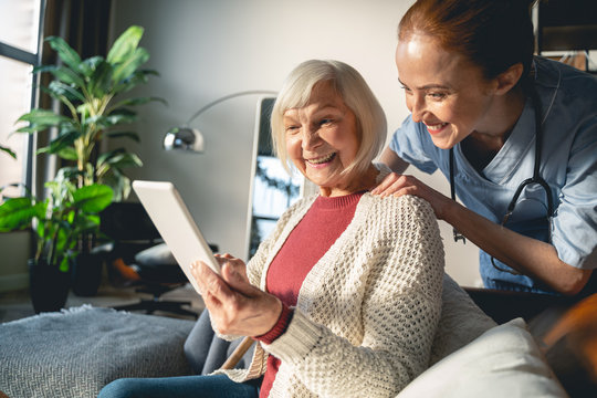 Positive delighted mature person using new device