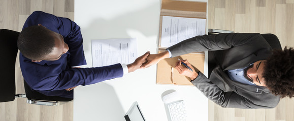 Young Businessman Shaking Hand With Candidate Over White Desk
