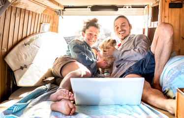 Digital nomad couple with cute dog using laptop on retro mini van transport - Travel life inspiration concept with indie people on minivan adventure trip watching pc on relax moment - Warm filter