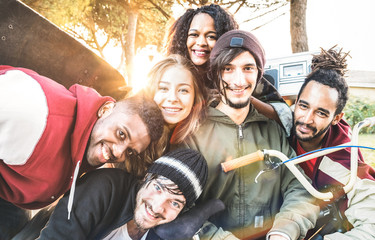 Multiracial best friends taking selfie at bmx skate park contest - Happy youth and friendship concept with young millenial people having fun together in urban city area - Bright warm sunshine filter