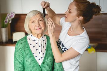 Papiers peints Salon de coiffure Cute young female person combing hair of her friend