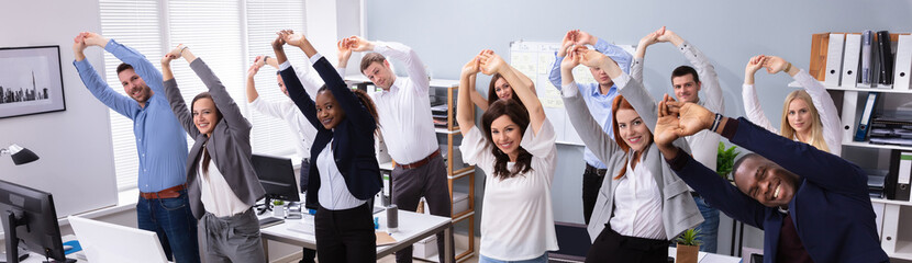 Young Businesspeople Doing Stretching Exercise At Workplace