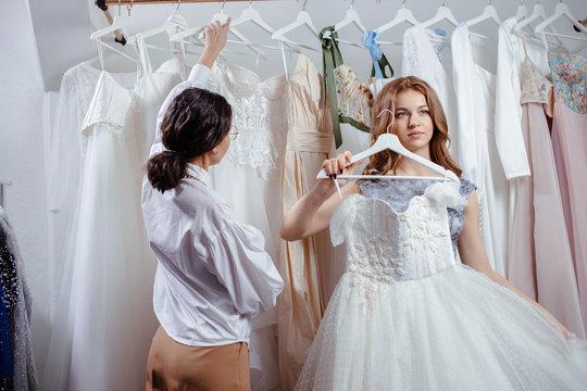 professional caucasian woman designer and bride preparing for wedding in salon, romantic atmosphere.