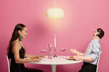 Positive Asian woman enjoys romantic dinner date with inflatable man, looks at her lover, spend time together, pose in modern restaurant at festive table, pink background. People, dating concept