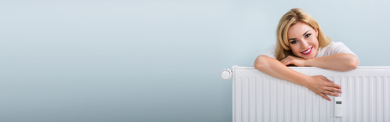 Woman In Sweater Leaning On Radiator Wall mural