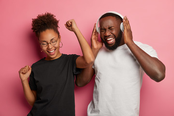 Photo of joyful Afro American couple have fun and dance to loud music, celebrate successfully...