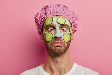 Fototapeta Close up portrait of man with crossed eyes, eager to have perfect skin, applies vegetable facial mask and cucumbers, wears shower cap, gets cosmetic procedures from beautician, isolated on rosy wall obraz