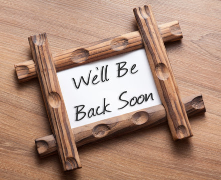 Text We'll Be Back Soon written on wood frame
