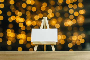 Mock Up mini easel with a white business card. Against the backdrop of a bokeh of stars garland.