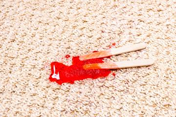Red Popsicle melting on carpet