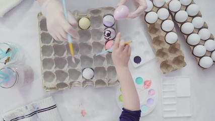 Wall Mural - Flat lay. Little girl painting craft Easter eggs with acrylic paint.