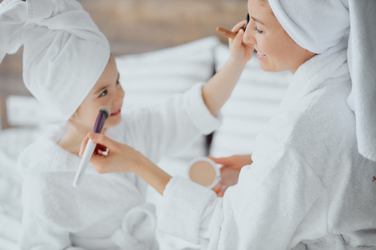 caucasian woman and little daughter sit on bed wearing towels and bathrobe doing makeup after shower. family concept