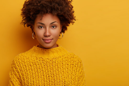 Portrait of Afro American millennial woman with calm serious face expression, looks directly at camera, wears knitted jumper, has natural beauty, models against yellow studio wall with empty space