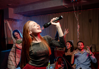 young caucasian woman with red hair sing in karaoke bar, wearing party clothes, have good voice to...