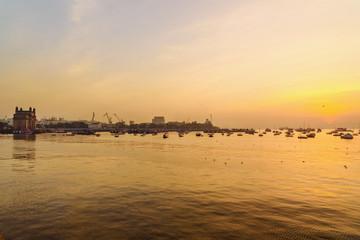 Gateway of India and fisherman boats in water of Arabian Sea on sunrise. Mumbai. India