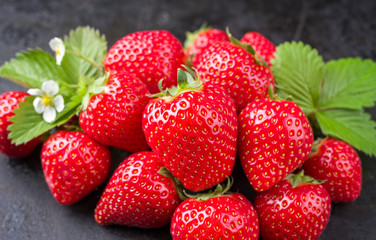 Fresh ripe strawberries offered as closeup on black rustic board as background