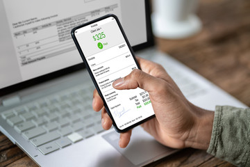 Businessman's Hands Working On Invoice On Smartphone