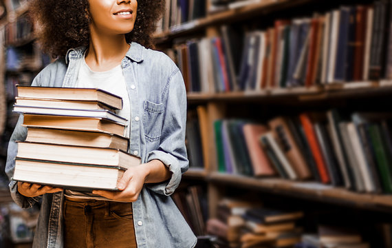 Photo for background, place for insertion, African American woman student holding a heavy armful of books in her hands against the background of bookshelves in a library. Learning concept, lifestyle