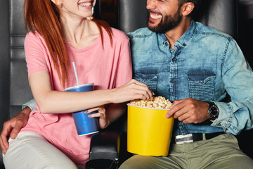 laughing diverse couple spending great time at the cinema, close up cropped photo. man and woman...