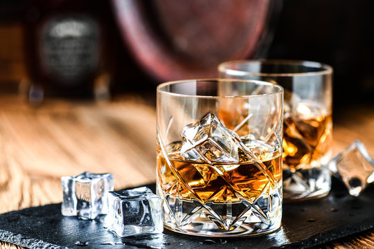 Glass of whiskey with ice cubes on black stone table. Side view with copy space alcohol concept.