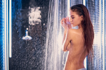 gentle slim caucasian woman with naked back stand in shower bath, under running water. female with long hair. spa