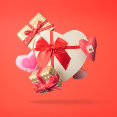 Valentines day creative composition with heart shapes and gift boxes. Levitating objects concept on red background.