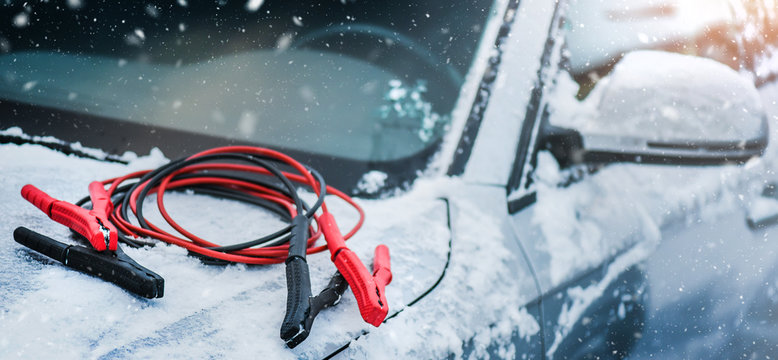 Charging cars battery with electricity trough electric cables. Vehicle jumper cable on car need starting or connection in winter time. Banner or panorama photo.