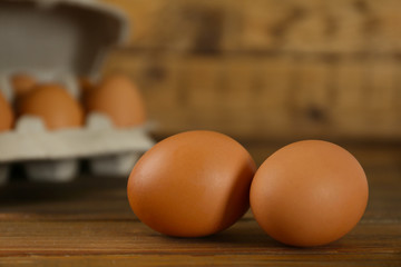 Raw brown chicken eggs on wooden table, closeup