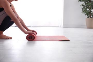 Foto op Textielframe School de yoga Woman rolling her mat on floor in yoga studio, closeup