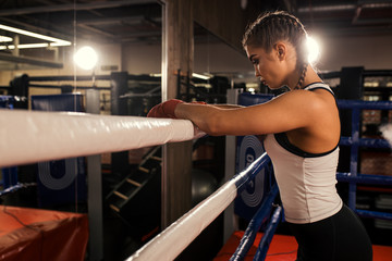 tired caucasian woman boxer stand leaning on the fence, after successful training in the ring. Sport concept