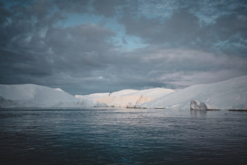 Foto auf Leinwand Grau Arctic nature landscape with icebergs in Greenland icefjord with midnight sun sunset sunrise in the horizon. Early morning summer alpenglow during midnight season. Ilulissat, West Greenland.