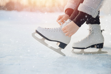 Girl ties shoelaces on white figure skates for ice rink in winter. Christmas holidays concept