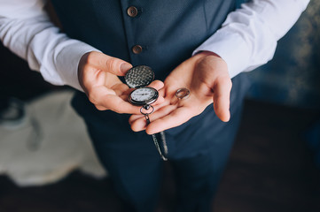 A man, a businessman in a suit holds in his hands a vintage, antique pocket watch and wedding rings close-up. The morning of the groom. Photography, concept, wedding. Clockwork.
