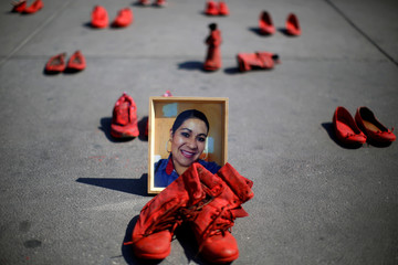 A framed photo of late Eugenia Machuca is placed next to pairs of women's red shoes, put on display by Mexican visual artist Elina Chauvet to protest against gender violence and femicide, at Zocalo square in Mexico City