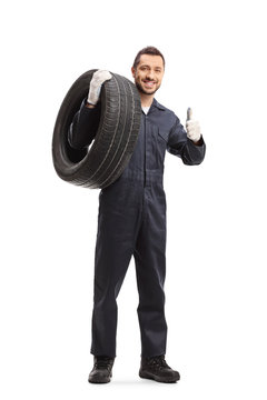 Auto mechanic carrying a tire and showing a thumb up sign