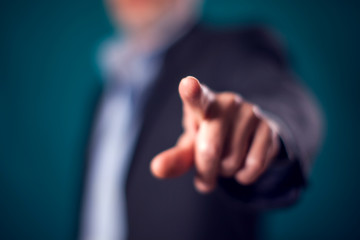 Businessman in suit point finger at camera in front of black background
