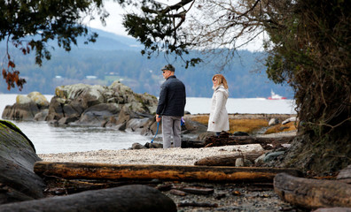 A couple walks on the beach outside a property, where according to British news reports Britain's Prince Harry and Meghan, Duchess of Sussex, spent the holidays in North Saanich