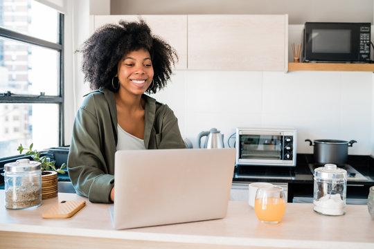 Latin woman using laptop at home.