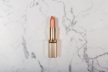 Golden lipstick on white marble background. Flat lay. Top view