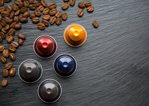Colorful Coffee Capsules and Coffee Beanson Grey Black Background Top ViewNatural Light Selective Focus.