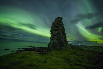 Poster Groen blauw Aurora Borealis (Northern Lights) above rocks