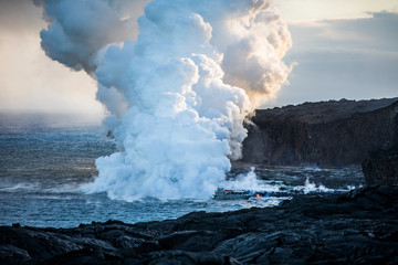 Lava pouring into the sea causing steam clouds