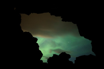 Wall Mural - Aurora Borealis (Northern Lights) above a cave entrance