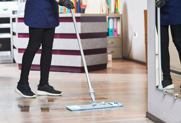 cleaning service. wiping office floor with mop