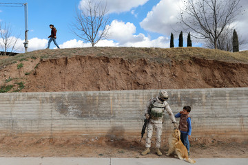 A soldier plays with a dog and a mormon child in La Mora