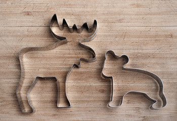Stainless steel moose and bear shape on wood board. Animal cookie cutter. Patriotic symbol of Canada. Silver outline.