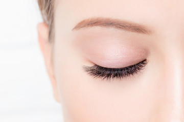 Closed female eye with beautiful makeup and long lashes on white background. Concept eyelashes extensions procedure