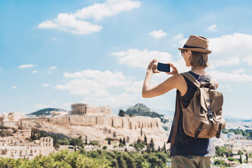 Photo sur Aluminium Athenes Young woman using smart phone in Athens with Acropolis at the background. Traveler girl enjoying vacation in Greece. Summer holidays, vacations, travel, tourism, technology concept.